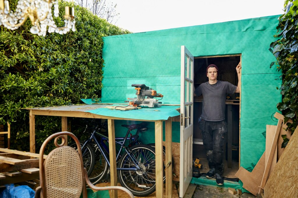 Portrait of man standing in doorway of garden shed used for carpentry